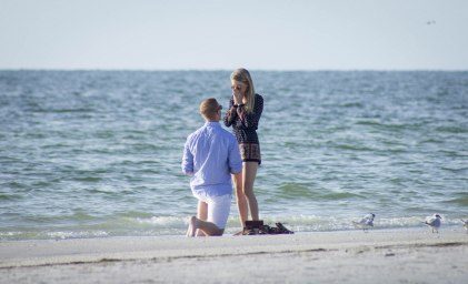 kneeling down at the beach engagement photo